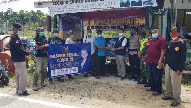 Anggota DPRD Provinsi Kaltara dari Partai NasDem Supa'ad Hadianto menyerahkan bantuan sembako kepada masyarakat melalui Kampung Trengginas Kampung Satu. Foto : Fokusborneo.com