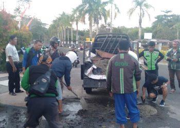 Komunitas Driver Online lakukan aksi peduli tambal jalan berlubang di Tarakan. Poto: ADO Kaltara