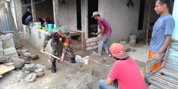 Babinsa Koramil 0907/01 Tartim Sertu Supriadi membantu warga binaannya dalam membangun rumah,Jumat(27/9).Poto: Pendim 0907/Trk