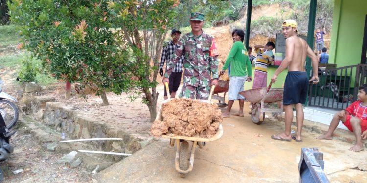 Sertu Supriadi yang turut serta membantu kerja bakti pembersihan material tanah longsor akibat hujan di Mushola Al - Jannah Kel. Mamburungan.Poto:Pendim0907/Trk