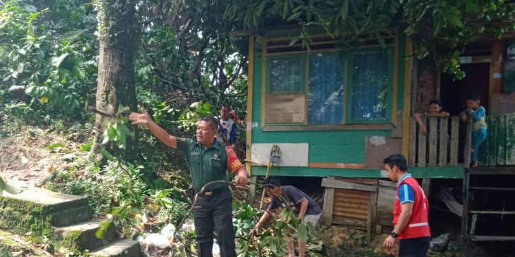 Serma Suprianto, mengajak masyarakat setempat dibantu BPBD kota Tarakan gotong-royong membersihkan pohon tumbang yang tepat mengenai atap rumah warga. Poto:Pendim 0907/Trk