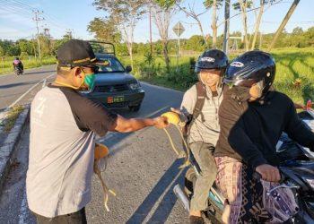 Ketua KPU Kota Tarakan Nasruddin bagikan masker ke pengendara roda 2 dan 4 di Simpang  Lampu Merah Keramat, Kamis (30/4). Foto : Istimewa