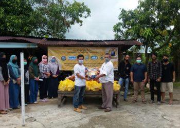 Dekan Fekon UBT Syaiful menyerahkan bantuan kepada mahasiswa Fekom yang tidak bisa pulang kampung, Jumat (8/5). Foto : Istimewa