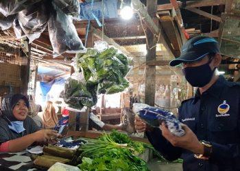 Sekretaris DPW Partai Nasdem Kaltara Supaad Hadianto membagikan masker kepada pedagang di Pasar Tenguyun, Kamis (21/5). Foto : Fokusborneo.com