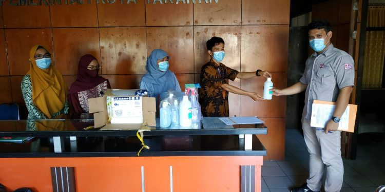 Staf Sekretariat KPU Kota Tarakan menyerahkan APD ke petugas Sekretariat PPK dan PPS, Kamis (25/6). Foto : Istimewa