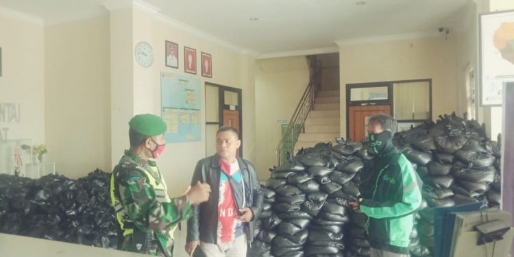 Babinsa Kodim 0907 Tarakan membantu mendistribusikan paket sembako tahap ke 2 Pemkot Tarakan, Sabtu (27/6). Foto  : Istimewa