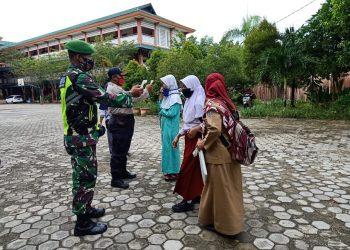 Babinsa Kodim 0907 Tarakan membantu panitia PPDB cek suhu badan orang tua siswa yang melakukan daftar ulang, Senin (29/6). Foto : Humas Kodim 0907 Tarakan