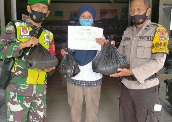 Babinsa Koramil 0907/02 Tarteng Sertu Arifin bersama rekan Babinkamtibmasnya membantu penyaluran sembako.Foto: Pendim 0907/Trk