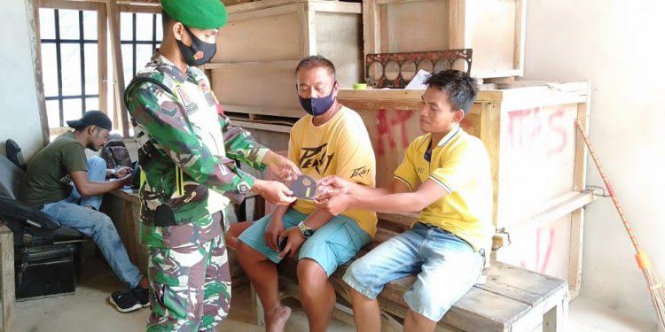 Babinsa Koramil 0907/02 Tarteng Sertu Arifin membagikan masker kepada warga yang ia temui disela-sela kegiatan komsosnya. Foto : Doc.Babinsa