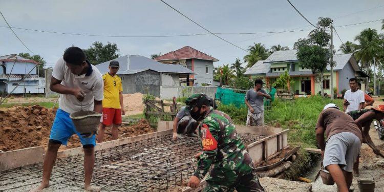 Babinsa Koramil 0907/02 Tarteng Serma Sinaga Membantu Warga Dalam Proses Pembangunan Jembatan. Foto: Doc.Babinsa