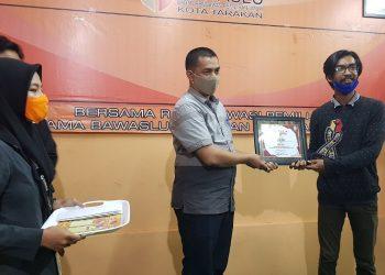 Ketua Bawaslu Kota Tarakan Zulfauzy Hasly menyerahkan hadiah dan piagam perlombaan, kepada pemenang lomba. Foto : Fokusborneo.com