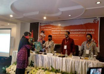 Anggota  KPU Kota Tarakan Jumaidah menyerahkan hasil rekapitukasi pemutakhiran data pemilih kepada Ketua KPU Provinsi Kaltara Suryanata Al Islami, Selasa (15/9). Foto : Istimewa