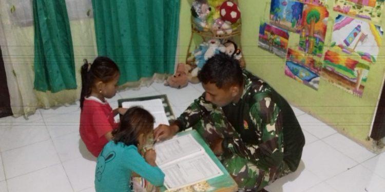 Mengisi Waktu Senggang : Sertu Taufik dari Kodim 0907 Tarakan mengajari anak anak pak shaleh di rumah induk semang pada malam hari. Foto: Penerangan Kodim 0907 Tarakan