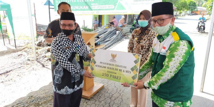 Ketua Baznas Nunukan Zahri Fadli (kanan) menyerahkan bantuan pakaian seragam sekolah secara simbolis kepada Kemenag Nunukan HM Saleh, Kamis (7/1). Foto: Istimewa