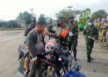 Danrem 092/Maharajalila, Brigjen TNI Suratno, S.I.P,  memberikan masker kepada warga yang tidak menggunakan masker saat berkendaraan. Foto: Penerangan Korem 092/Mrl