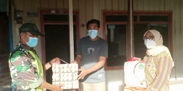 Babinsa Koramil 0907/02 Tarakan Tengah, mendampingi pengurus posko covid tingkat RT menyerahkan bantuan sembako untuk meringankan beban warga.Foto: Doc.Babinsa