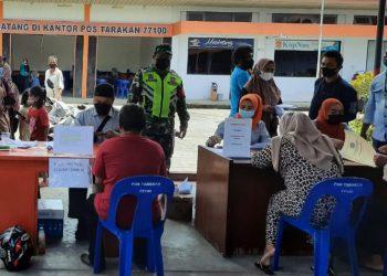 Babinsa Kodim 0907 Tarakan, saat membantu pengamanan penyaluran Bantuan Sosial Tunai (BST) tahap IV di wilayah binaan masing - masing.Foro: doc.Babinsa