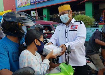 Ketua KKMB membagikan makanan takjil kepada pengendara yang melintas di Simpang Empat THM  Sabtu (24/4). Foto : Fokusborneo.com