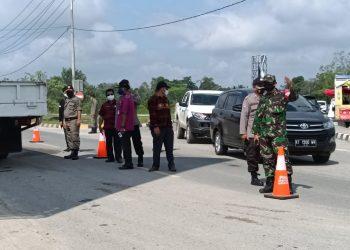 Petugas gabungan pos penyekatan saat melakukan pemeriksaan  masyarakat yang akan masuk Kota Samarinda