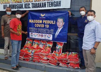 Anggota DPRD Provinsi Kaltara dari Partai NasDem Supa'ad Hadianto menyerahkan bantuan sembako kepada masyarakat melalui Kampung Trengginas Pamusian. Foto : Fokusborneo.com