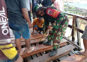 Babinsa Koramil Tarakan Timur, saat membantu warga melakukan perbaikan jembatan bersama warga di RT.5 Kelurahan Pantai Amal.Foto:Doc.Babinsa